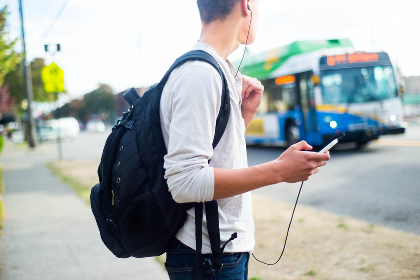 A side view of a young man waiting for the bus while listening to music on his phone.